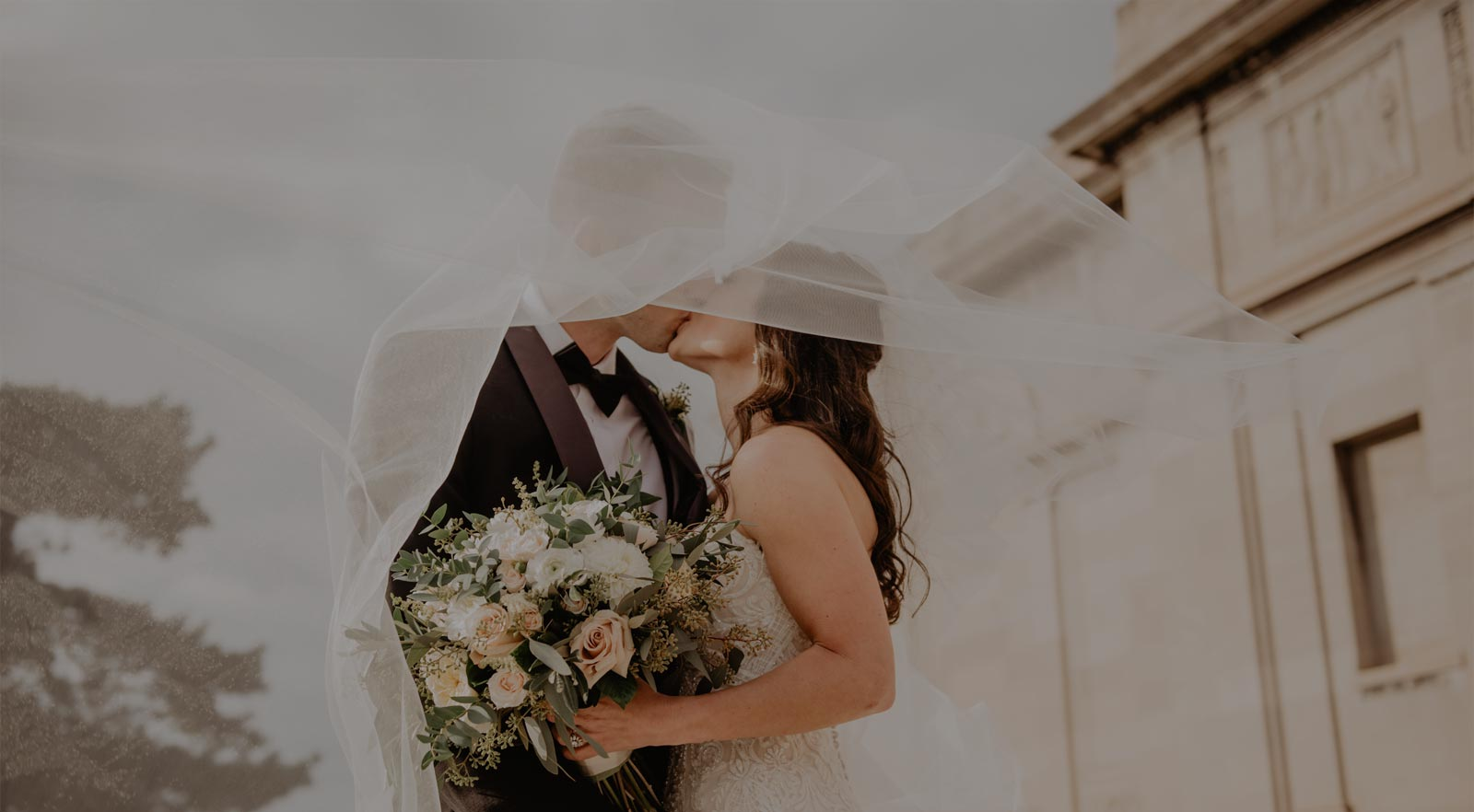 Photo of a bride and groom kissing as the bride's veil swirls around the newlywed couple