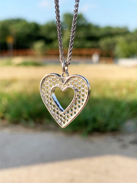 Photo of a silver heart pendant on a chain with a pretty green field in the background