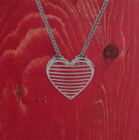 Photo of a heart pendant on a red barn board background