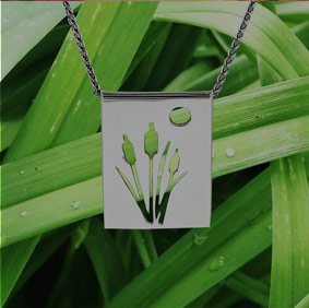 Photo of a pendant with a cattail design over green grass